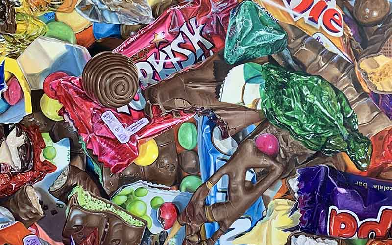 Painting by Fine Art graduate Emilia Symis showing piles of chocolate in and out of their bright wrappers