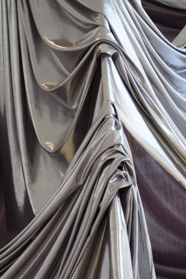 Emily Cannell - Close up of silver fabric draped across a sculpture, ruched and catching the light