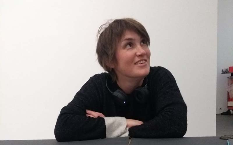 A woman with cropped brown hair and a dark jumper leaning crossed arms on a table and smiling up to her left