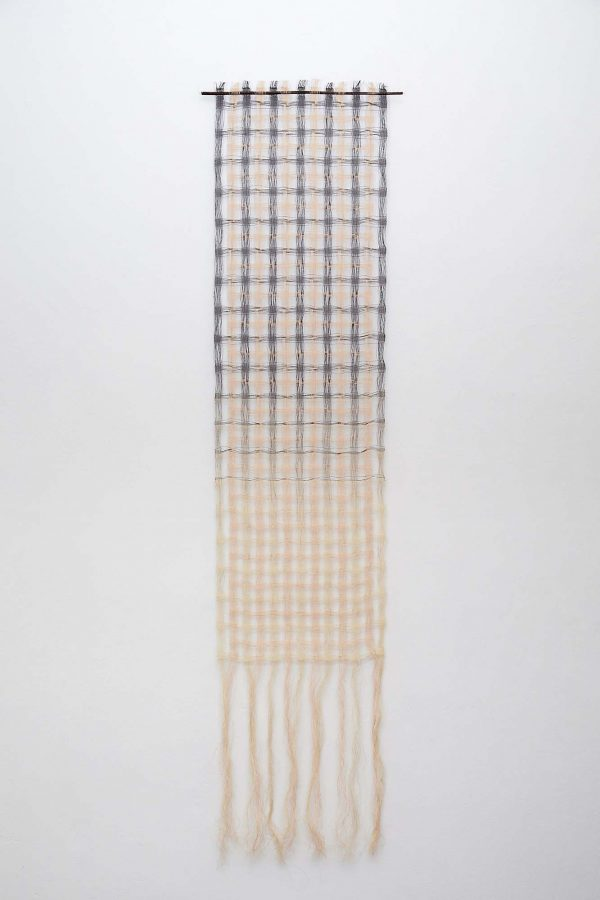 Lizzie Kimbley - Long rectangular textiles piece hanging on a white wall, made of woven squares in cream and blue