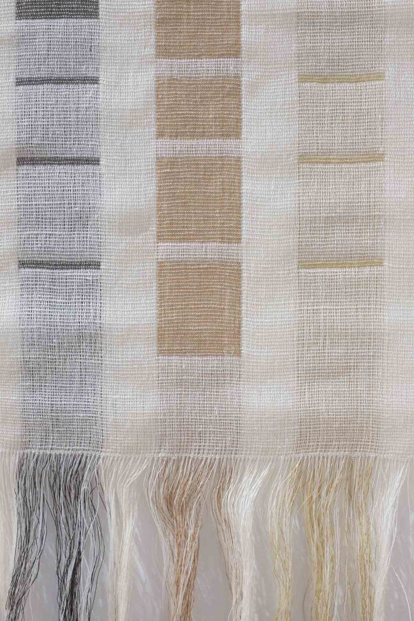 Lizzie Kimbley - Close up of a woven textiles piece hanging on a white wall and made up of grey and pale rust squares on a cream background