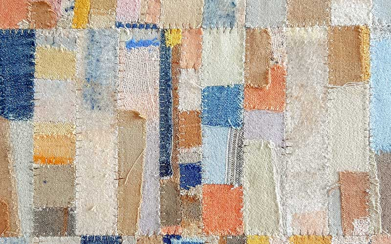 Close up of an MA Textile Design piece made up of many small squares and rectangles of fabric in soft peach, pink and blue tones