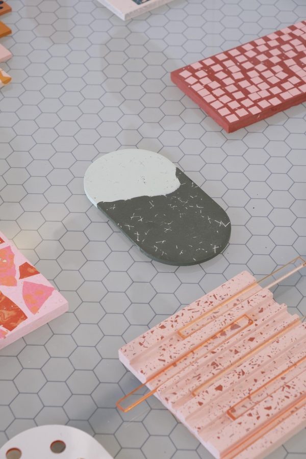 Victoria Paulley - A grey table with individual terrazzo pieces in pink, red, coral and grey in different shapes placed apart from each other