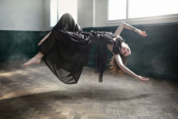 Annabel Leech - Photo by Kev Foster showing a woman in a black dress levitating horizontally with her arms above her head in soft natural light