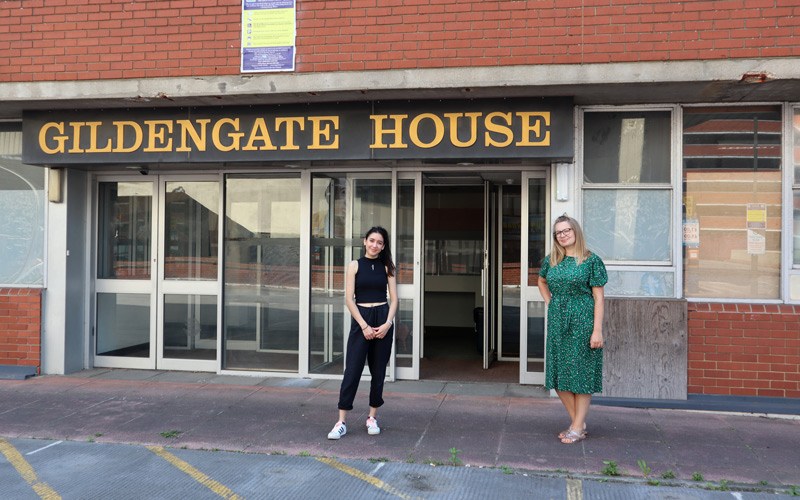 BA Textile Design graduates Gabriela Sokolowska and Morgan Geller stand outside the entrance to Gildengate House in Norwich, where Outpost provide studios to approximately 90 artists.