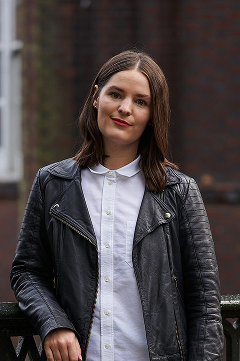 BA Fashion Marketing and Business Lecturer Holly Farrar stands for a profile photo in a leather jacket and white shirt, smiling at the camera