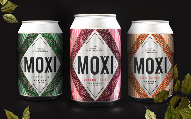 Packaging design by BA Graphic Design graduate Emily Frith. Three aluminium drinks cans are photographed on a black background, with green leaves around the edges. Each can has a silver diamond in the middle, with the word 'Moxi' in a black sans serif font. From left to right, a green tribal print for green apple tea, purple tribal pattern for dragon fruit tea, and orange tribal print for peach and apricot tea.