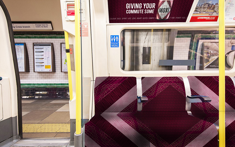 Brand extension for Moxi fruit tea by BA Graphic Design graduate Emily Frith. Inside a London tube train, the fabric on the seats is the same purple tribal pattern as the packaging of Moxi fruit tea. Above the seat, on the train wall, is an advert for Moxi tea