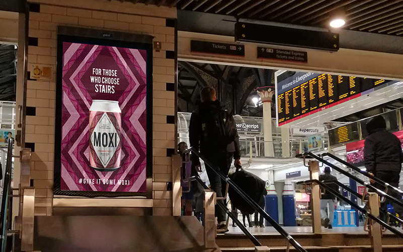Advertising design for Moxi fruit tea by BA Graphic Design graduate Emily Frith. A photograph of a London tube station. On the right, a commuter is walking up a flight of stairs. On the wall adjacent to him is a billboard poster for Moxi fruit tea. The poster is a geometric purple tribal pattern with a photograph of a can of Moxi tea.