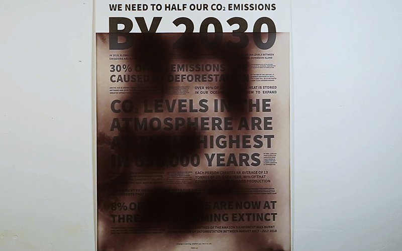 Typographic poster by BA Graphic Communication graduate Chloe Turner. The poster, white with black typography outlines the urgent need to reduce Co2 emissions and save our planet. The poster is printed with thermochromic ink, which responds to temperature. Parts of the poster have been heated, revealing text under black smoke-like colour.