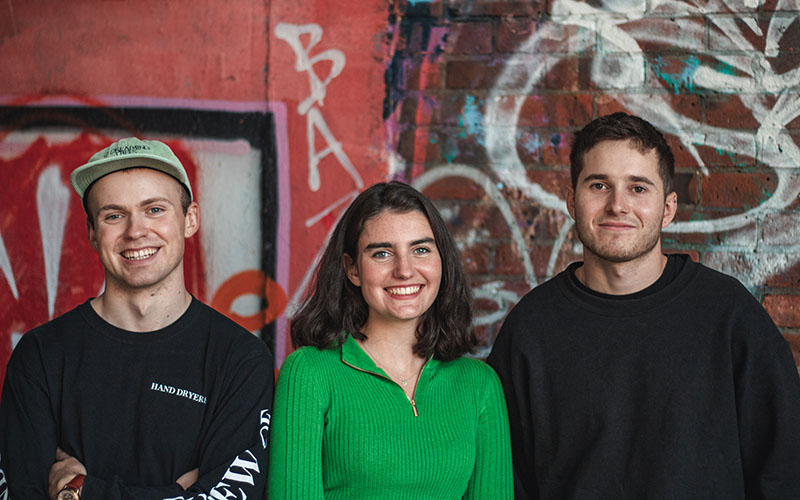 MA student Callum Ritchie standing with graduates Julia Triay and Dominic Lovegrove-Saville against a graffiti wall