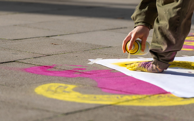 Close up of a person in a khaki jumpsuit spray painting yellow onto a pavement