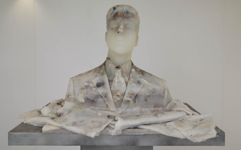 Male bust made out of white wax on a grey plinth