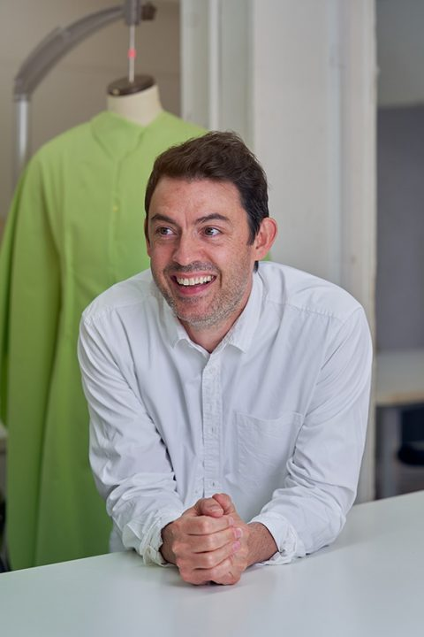 Eugene Reeder, BA Fashion Senior Lecturer at Norwich University of the Arts smiling and leaning on a bench in front of a fashion mannequin with a green garment on