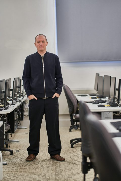 BA Games Art and Design Lecturer Jack Allen standing in computer lab at Norwich University of the Arts