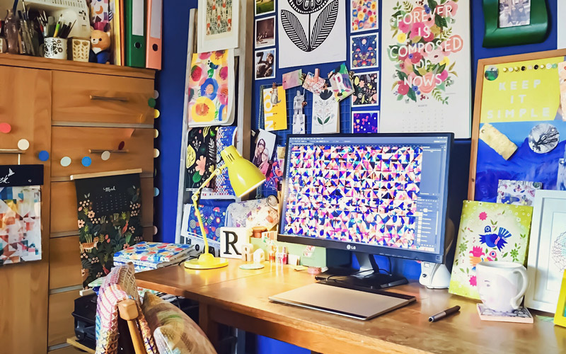BA Textile Design graduate Rachel Parker's home studio. Her wooden desk, with graphics tablet and monitor is up against a bright cobalt blue wall. On the wall is a gallery of colourful prints, calendars and embroidery, some created by Rachel.