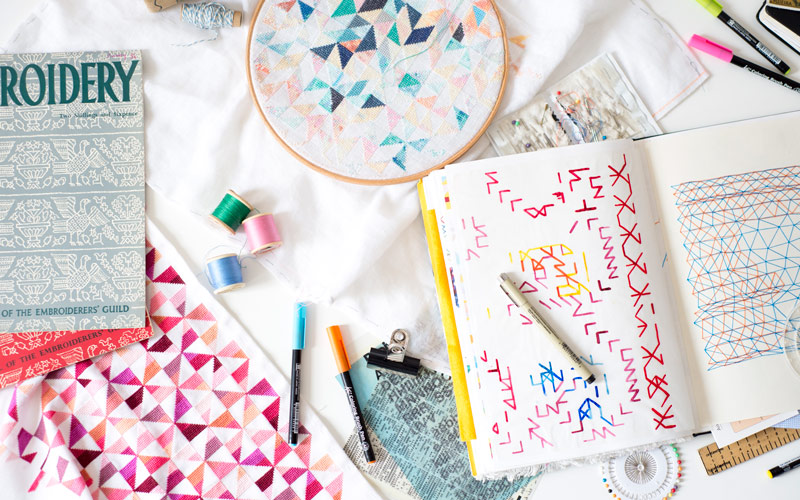 A flatlay of BA Textile Design graduate Rachel Parker's sketchbook and embroidery. The sketchbook is open on coloured lines drawn in a stitch style. Above the sketchbook is an embroidery hoop with geometric patterns embroidered in various shades of blue, green and pink thread. Pens and reels of thread are next to both the sketchbook and hoop, as well as an embroidery magazine
