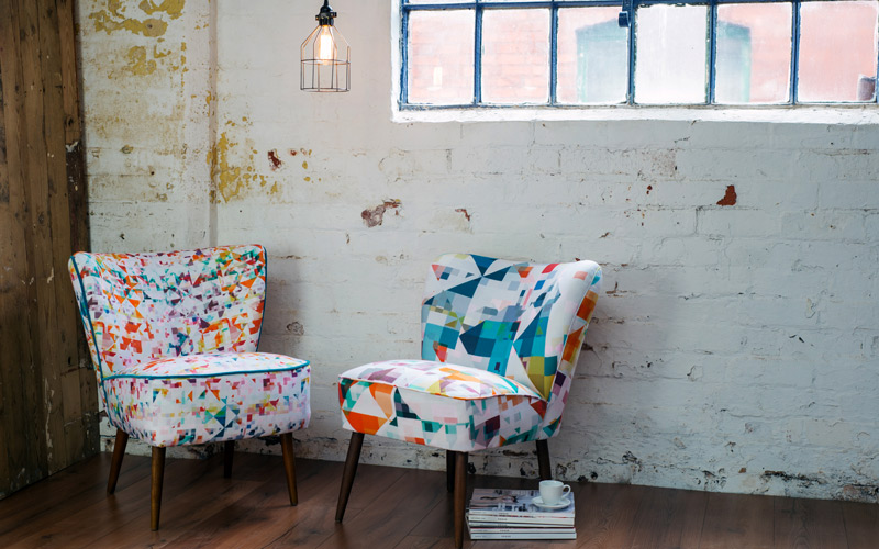 Photograph of two modern chairs in an industrial style warehouse. The chairs are upholstered in geometric print fabric, designed by BA Textile Design graduate Rachel Parker