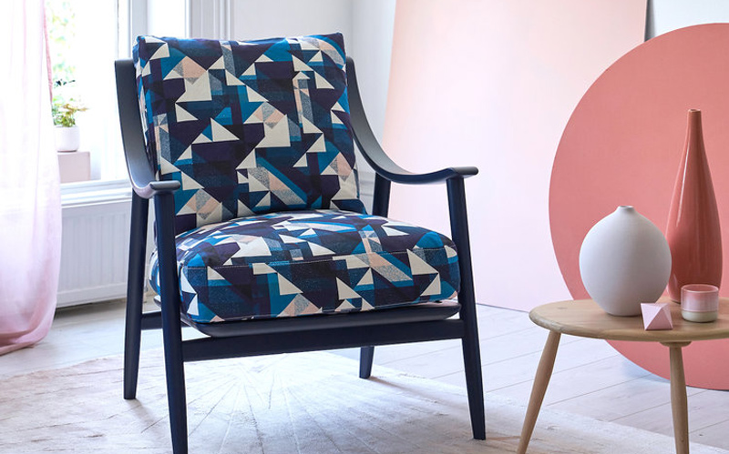A modern chair with a blue wood frame, upholstered in blue triangular geometric print designed by BA Textile Design graduate Rachel Parker