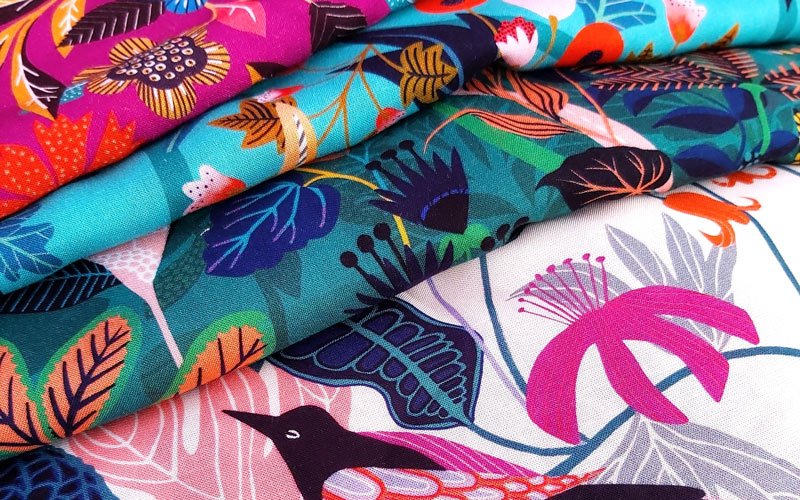 A pile of colourful, botanical print fabrics designed by BA Textile Design graduate Rachel Parker