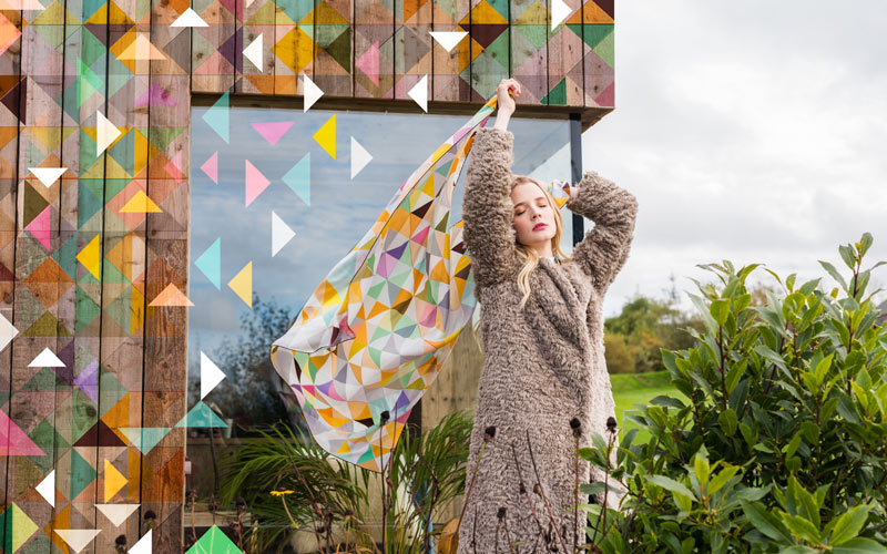 A blonde haired, fair skinned female model is standing with her hands above her head in front of a modern wood building. She is wearing a fluffy teddy coat. In her hands and blowing in the wind is a silk scarf with a geometric pattern, designed by BA Textile Design graduate Rachel Parker