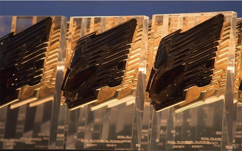 A blurred image of three gold awards next to each other