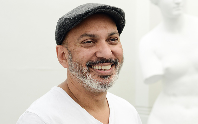 Professor Suri Krishnamma in a white tshirt and grey cap smiling