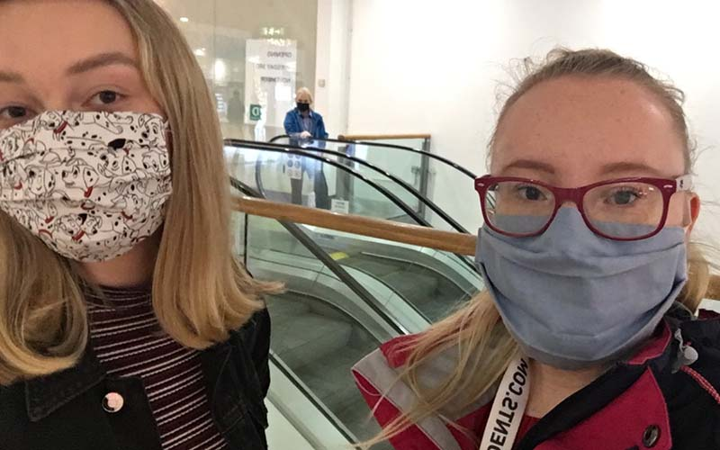 Acting students Abigail and Daniella wearing face masks and looking at the camera
