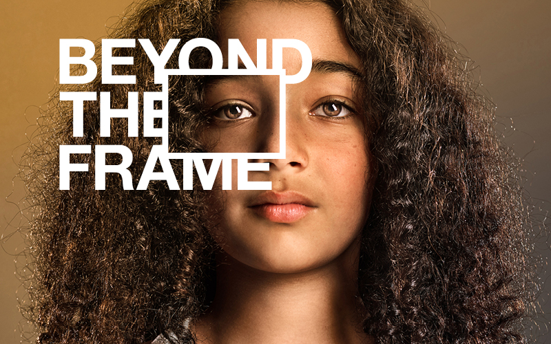 A girl with long curly brown hair looking at the camera with the white Beyond the Frame logo on top