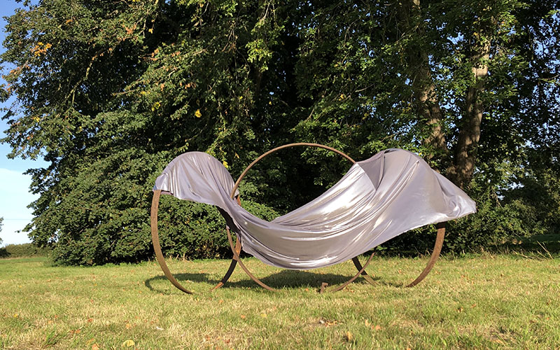 Silver fabric draped over a metal sculpture made of three large loops outside on green grass against trees