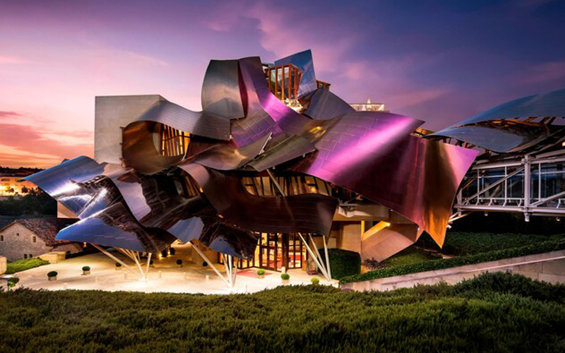 A photo of Spanish Hotel Marques De Riscal designed by architect Frank Gehry. The hotel has a sculpture-esque curvy sloping roof that look like folded pieces of steel on top of each other.