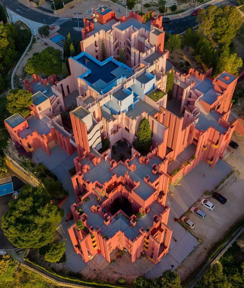 Aerial photo of La Muralla Roja, a residential apartment complex, in Spain. Pink blocky buildings with flat roofs, with a swimming pool in the shape of a cross.