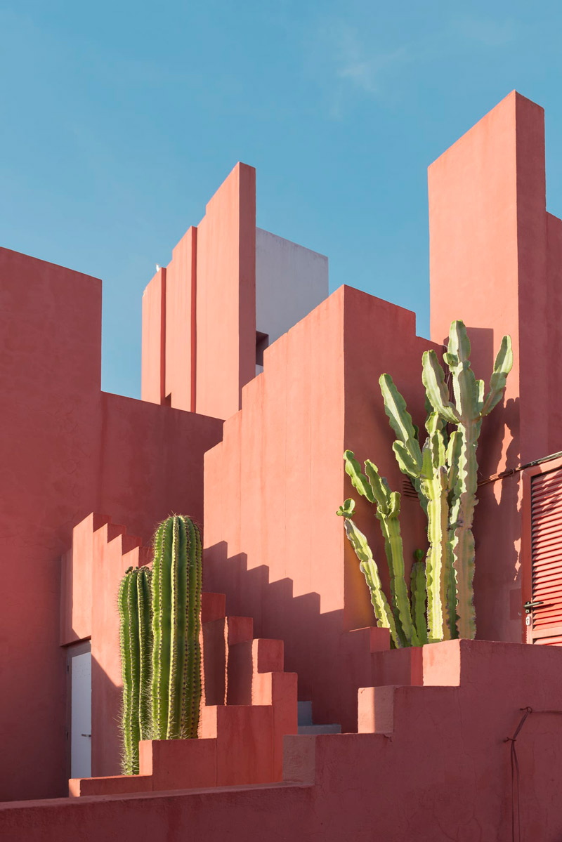 A photo of La Muralla Roja, a residential apartment complex, in Spain. Bright terracotta pink rectangular buildings pictured against a clear blue sky. Two large green cactus are placed either side of the stairwell.