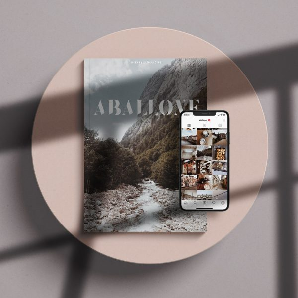 Aballone - Aballone magazine, designed and launched by BA Design for Publishing students Toby McLaren and Hannah Roadknight. A magazine laid on a pink background. A mountainscape is on the front cover, with the word 'Aballone'. On top of the magazine is an iPhone open on the Aballone instagram feed.