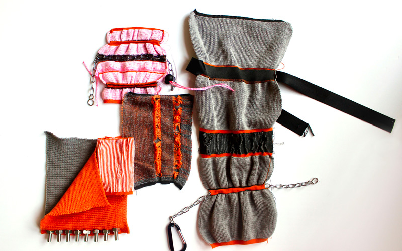 A flatlay of bright orange, grey and red textile weaves, with metal loops, nuts and chains intertwined. By BA Textile Design graduate Emma Cutts