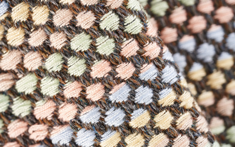 A close up shot of woven brown, peach, blue, yellow and green yarns, producing a circular repeat pattern. By BA Textile Design graduate Rebecca Bardwell-Dix