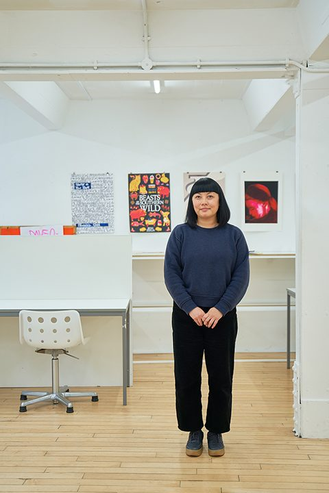 BA Illustration Lecturer Alice Lee standing in front of artwork in the Illustration studio at Norwich University of the Arts