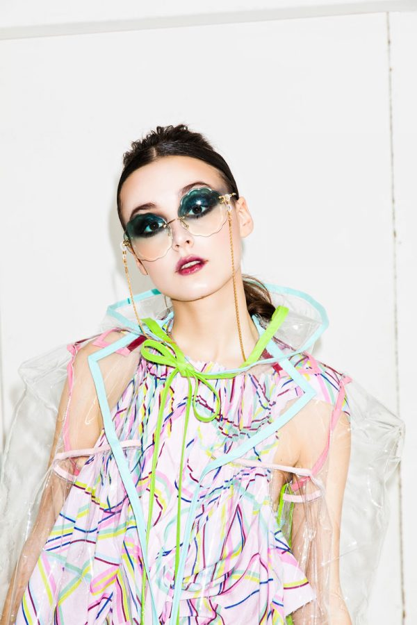 Alice Fox - White female model is wearing a transparent clear anorak, with pastel pink and blue edging. Underneath she wears a sleeveless white dress, with pink, blue, pastel blue and yellow lines. Designed by BA Fashion student Alice Fox