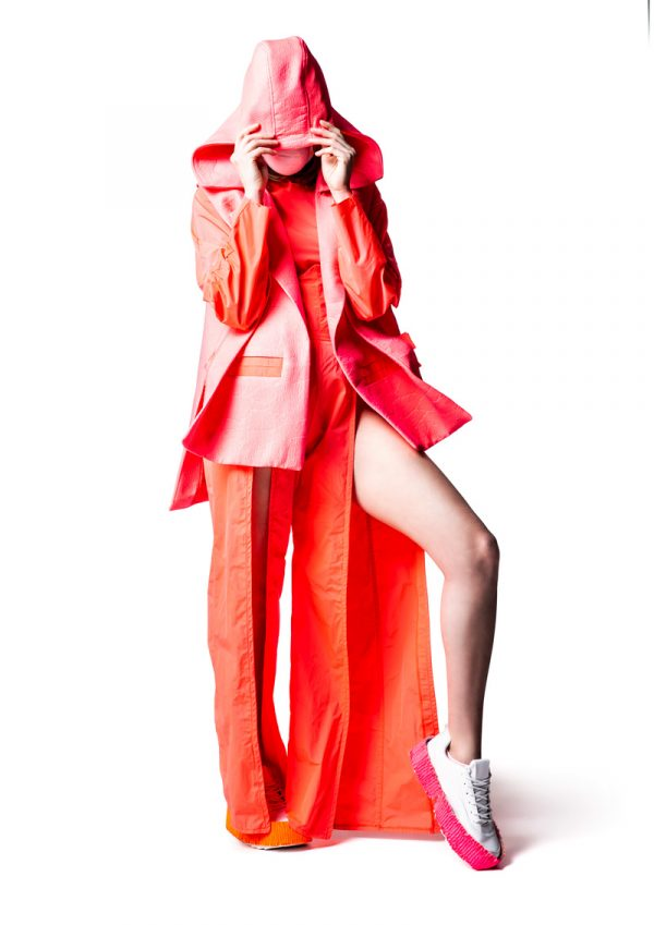 Annabelle Shortland - A female model wears a floor length neon pink split leg jumpsuit, with a neon pink jacket, hood up covering her face. Garment designed by BA Fashion student Annabelle Shortland