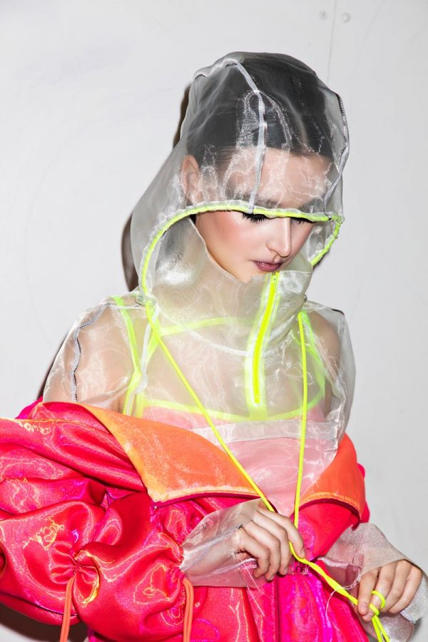 Anya Sims - White female model wears a layered neon pink, yellow and orange jacket, partially unzipped. Underneath is a transparent grey and neon yellow hooded top. Designed by BA Fashion student Anya Sims
