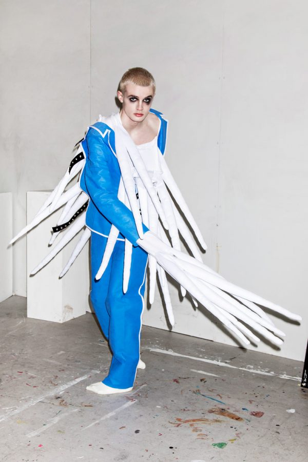 Charles Mead - White male model is photographed mid-twist, wearing a blue jacket and trousers resembling hospital scrubs. From the jacket hands and chest, long white tendrils dangle down. Garment designed by BA Fashion student Charles Mead