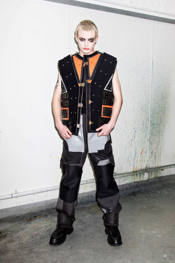 Chloe Last - White male model wears a sleeveless black and neon orange jacket, with industrial-style studded embellishment and geometric cuts of fabric. His trousers are black and grey, made from precisely cut shapes, with a variety of textures and buckles. Designed by BA Fashion student Chloe Last