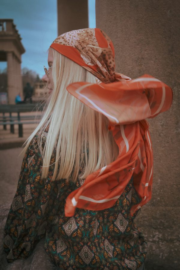 Amy Foster - A photograph from behind a female model with long blonde hair, wearing a red and white headscarf, which has caught the wind. Styled and photographed by BA Fashion Communication and Promotion student Amy Foster