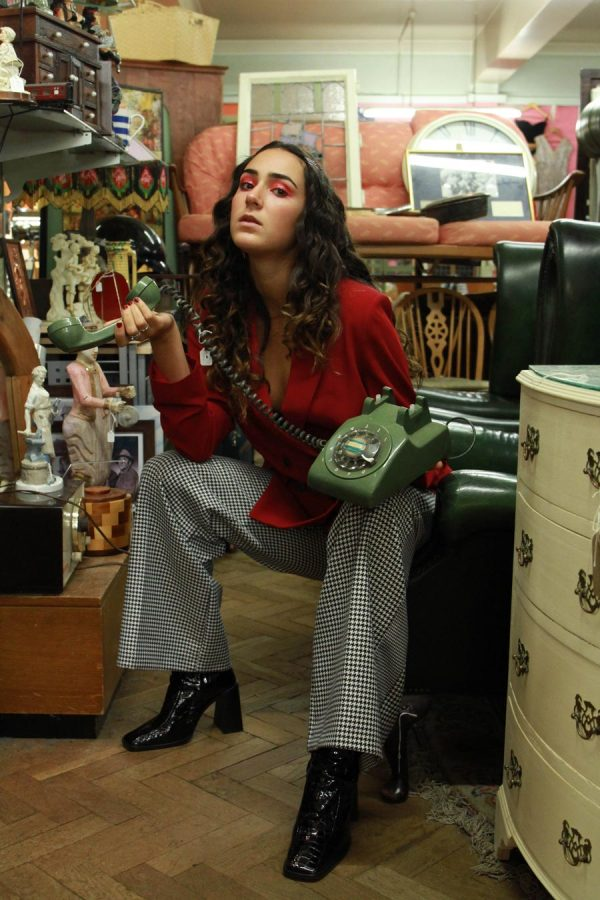 Ana Corona - Photo of a brunette female model sat in an old antiques shop, leaning forward, holding a green corded telephone in her hand. Styled and photographed by BA Fashion Communication and Promotion student Ana Corona