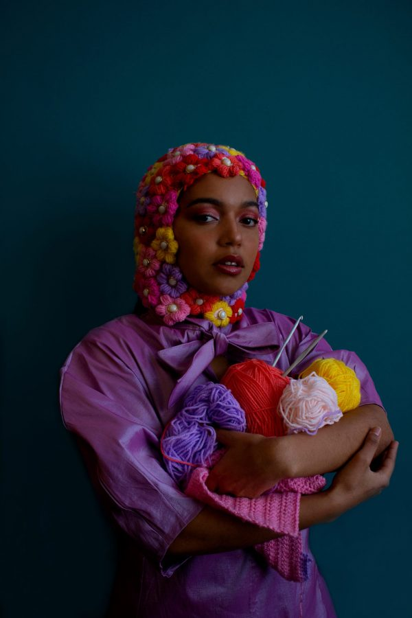 Emily Mitchell - Female model is photographed against a teal blue background, wearing a purple dress. On her head is a knitted balaclava, made out of lots of fabric flowers. She holds bundles of different coloured yarn in her arms along with some knitting needles. Styled and photographed by BA Fashion Communication and Promotion student Emily Mitchell