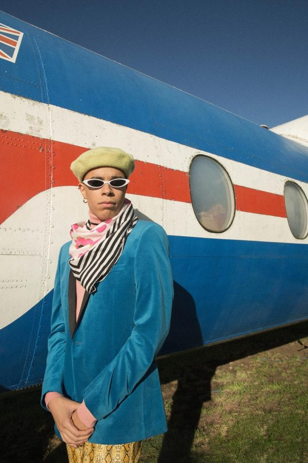 Jess Anderson - 80's style photo of a mixed race male model standing in front of a vintage aircraft. He wears a blue velvet blazer, with a patterned scarf, sunglasses and beige hat. Work by BA Fashion Communication and Promotion student Jess Anderson