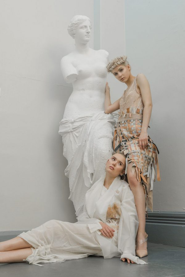 Sophie Anderson - A photograph of two female models and a statue in a grey corridor. One model is standing and leaning on the statue wearing a sleeveless textured dress, the other model is laying at her feet, wearing all white. By BA Fashion Communication and Promotion student Sophie Anderson