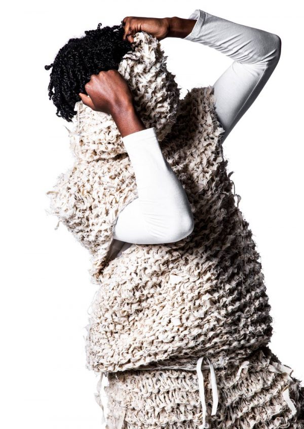 Hillary Marerwa - Black male model wearing a long sleeved white t-shirt, with a sheep's wool-like knitted short sleeved jumper over the top, with matching wool shorts. The model is pulling the loose collar up over his face. Garment designed by BA Fashion student Hillary Marerwa