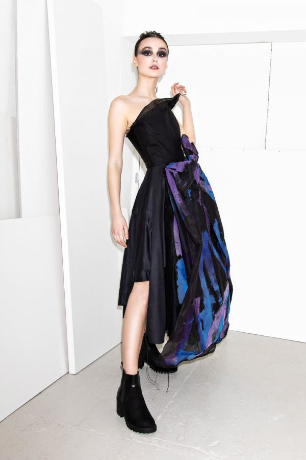 Lorna Mellowes - White female model is wearing a black bandeau top dress, fitted at the top and loose flowing from the hips. The skirt is made from black, blue and purple coloured fabric, representing geodes. Designed by BA Fashion student Lorna Mellowes