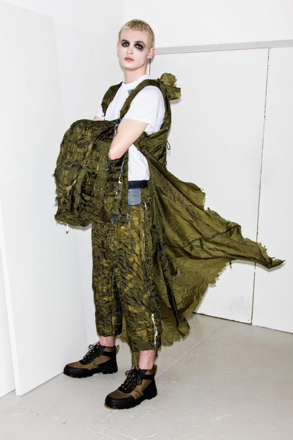 Martha Havard - White male model is wearing a white tshirt, with cropped khaki green trousers, a khaki green sleeveless cape that looks torn, whilst holding a khaki green jacket in crossed arms. Garment inspired by WW2 parachutes and designed by BA Fashion student Martha Havard